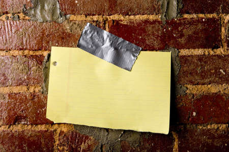 taped: A blank sheet of paper taped to a brick wall with copy space Stock Photo