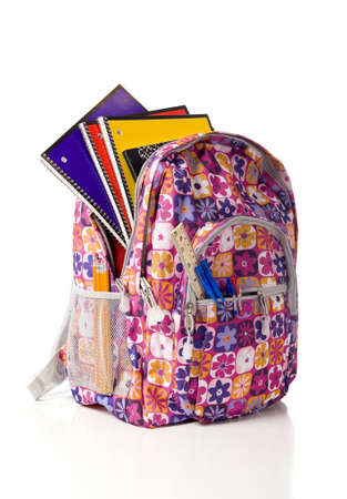 A pink school backpack overflowing with school supplies on a white background with copy space photo