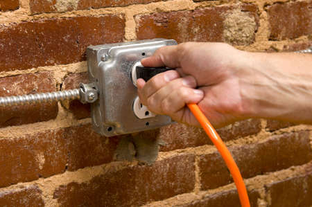 a mans hand plugging in an extension cord in  a junction box electrical outlet on a brick wall, connecting concept photo