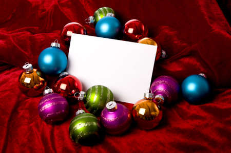 A blank notecard surronded by Christmas decoration or baubles on a red background, add copy or graphic.  Christmas Party Invitation or communication
