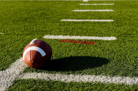 terrain foot: Un cuir marron de football am�ricain sur un terrain de football vert
