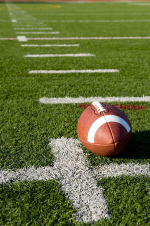 american football field: A brown leather American football on a green football field