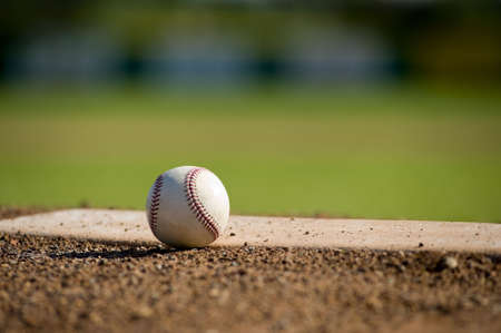 dirt: A white leather baseball lying on top of the pitchers mound at a baseball field with copy space