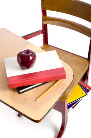A vintage school desk with school books, a red apple and a pencil on a white bacground with copy space photo