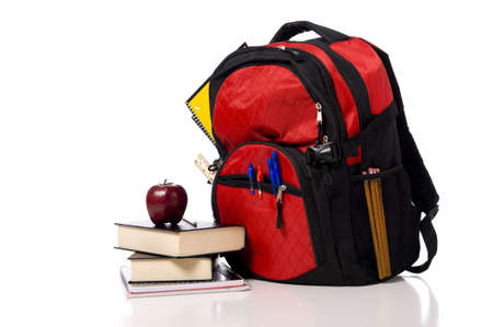 school supplies: A red school back pack or book bag overflowing with school supplies including, notebooks, pens, pencils, rulers and glue, books and an apple
