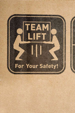 instructing: A safety label on a cardboard box instructing to team lift