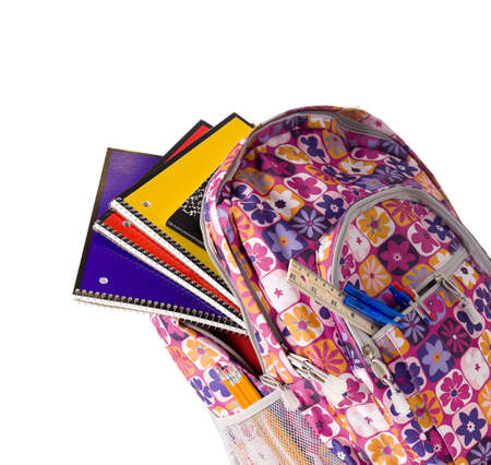bookbag: A pink school backpack overflowing with school supplies on a white background with copy space