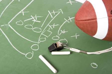 A diagram of a football play on a chalkboard with a football, chalk, eraser ane a whistle Stock Photo