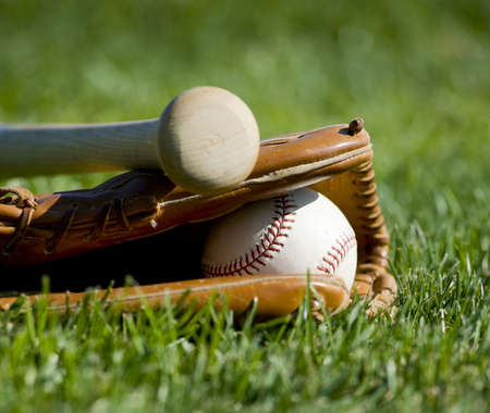 A baseball field with a leather baseball glove, a ball and a wooden bat