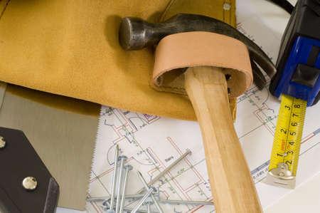 leveringen van een bouwvakker of een handige man, waaronder een hamer, meetlint, spijkers, gereedschap gordel en blauwe prints of plannen Stockfoto