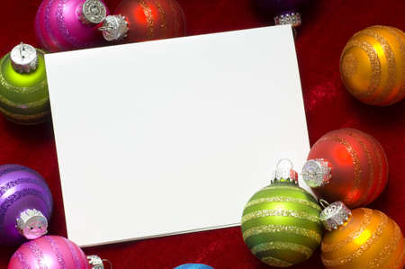 A group of colorful Christmas baubles or ball surrounding a white notecard with copy space