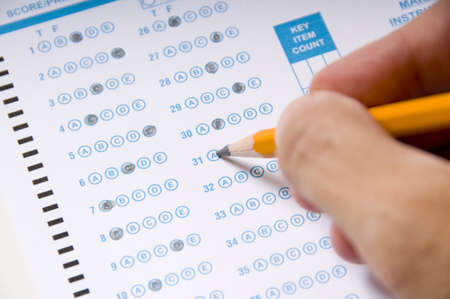 filling in: A hand holding a yellow pencil filling in a computer checked answer sheet on an examination.  Education concept Stock Photo