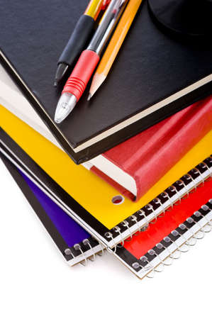 notebook: A stack of school books and spiral notebooks with a pencil and pens on tops in front of a white background