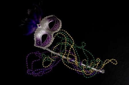 colorful beads: A Mardi Gras or constume party mask with beads on a black background