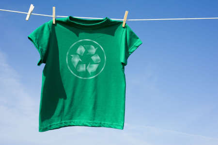 A green t-shirt hanging on a clothesline with the recycle symbol on the front,  environmental or recycling theme Imagens - 4754028