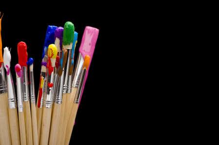 Een groep van een multi-color painbrushes op een zwarte achtergrond Stockfoto