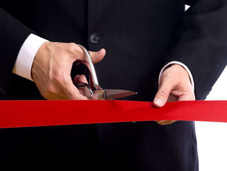 taglio del nastro: Un uomo d'affari che indossa un abito blu di taglio un nastro rosso con un paio di forbici d'argento lucido. Grande cerimonia di apertura o di un evento