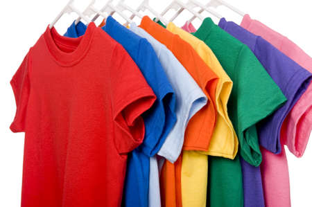 A row of colorful row t-shirts hanging on hangers on a white background Foto de archivo