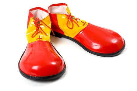 with humor: A pari of oversized red and yellow clown shoes on a white background Stock Photo