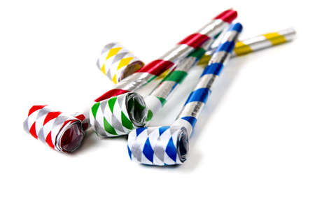 party favors: A group of colorful party noisemakers on a white background.  New Years Eve or birthday theme Stock Photo