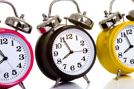 A group of colorful, traditional alarm clocks on a white background, time concept photo