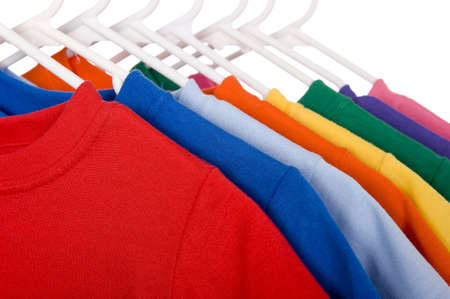 A row of colorful row t-shirts hanging on hangers on a white background Imagens - 5193712