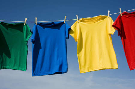 A row of colorful row t-shirts hanging on hangers on a blue sky background Imagens - 5193418