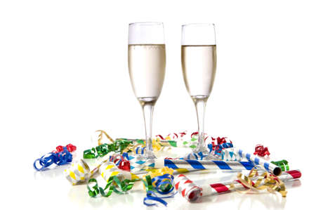 Two glasses of champagne with party noise maker and streamers on a white background.  New Year's Eve theme
