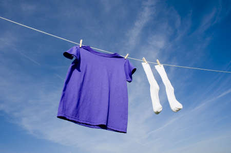 A purple blank t-shirt hanging on a clothesline with a pair of white socks in front of a blue cloudy sky Imagens