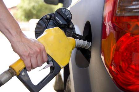 A hand holding a gasoline nozzel pumping gasoline into a car photo