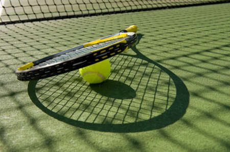 A tennis racket and new tennis ball on a freshly painted tennis court