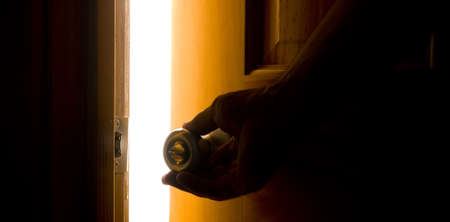 A hand opening a door with a bright light