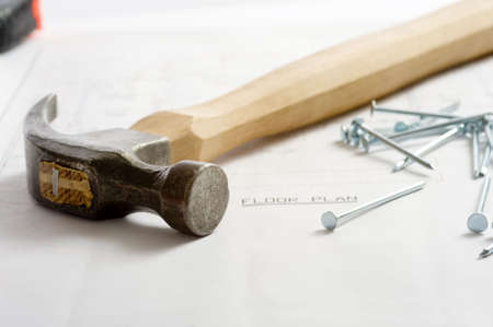 A floor plan with hammer, nails lying on top Stock Photo