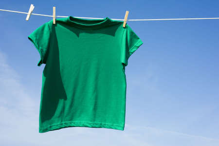 A green t-shirt hanging on a clothesline in front of a blue sky Stock fotó