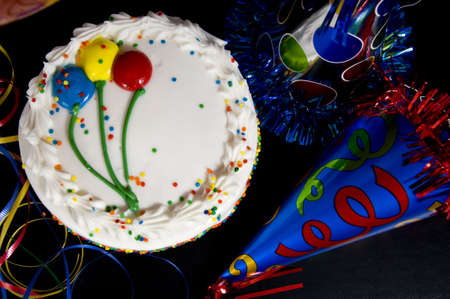 A white birthday cake surrounded by colorful party hats and ribbon streamers Stock fotó