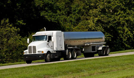 wheel truck: A fuel tanker transport truck on a highway, fuel transportaion