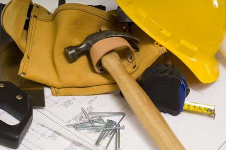 levering van een bouwvakker of een handige man, waaronder een hamer, meetlint, spijkers, gereedschap riem en blauwe afdrukken of plannen