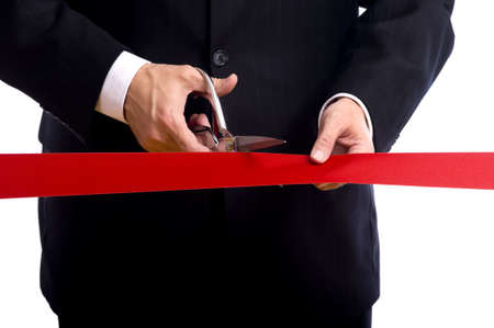 silver ribbon: A business man wearing a blue suit cutting a red ribbon with a pair of shiny silver scissors.  Grand opening ceremony or event