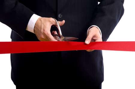 tijeras cortando: Un hombre de negocios con un traje azul de corte de una cinta roja con un par de tijeras de plata brillante. Ceremonia de inauguraci�n o evento de Foto de archivo