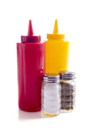 A cafe or restaurant tabletop setup with ketchup and mustared bottles and a salt and pepper shakers photo