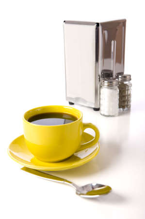 A cafe or coffee shop tabletop setup with a yellow cup and saucer, spoon, napkin holder, salt and pepper shakers and codiment bottles on a white background Фото со стока