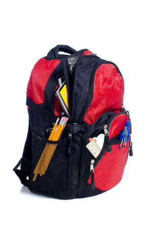 notebook: A red school back pack or book bag overflowing with school supplies including, notebooks, pens, pencils, rulers and glue
