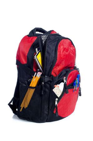 utiles escolares: Una mochila escolar de color rojo o bolsa de libros rebosantes de material escolar, incluidos, cuadernos, bol�grafos, l�pices, reglas y pegamento