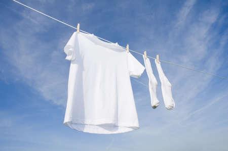 Un t-shirt blanc à blanc suspendu à une corde à linge devant un fond de ciel bleu à l'espace de copie