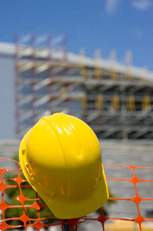 A construction site with a protective helmet or head gear with the building or structure in the background