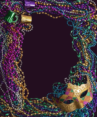 bead: A group of mardi gras beads and mask making a frame with copy space on a purple background