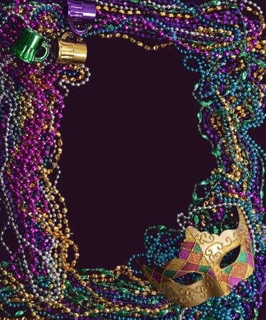 mardi gras: Un gruppo di sfere mardi gras e di maschere una cornice con copia spazio su un fondo viola