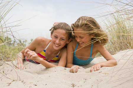 Two young female children playing in the sand at the beach photo