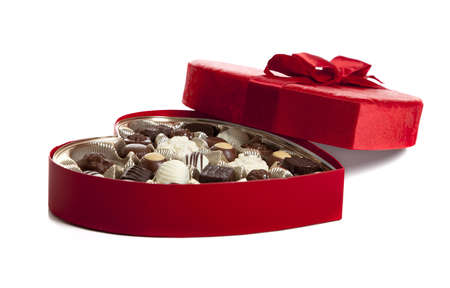 A red heart shaped box of Valentines chocolate on a white background with copy space photo