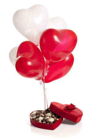 A Valentines day background consisting of chocolates in a heart shaped box and heart shaped balloons on a white background Imagens